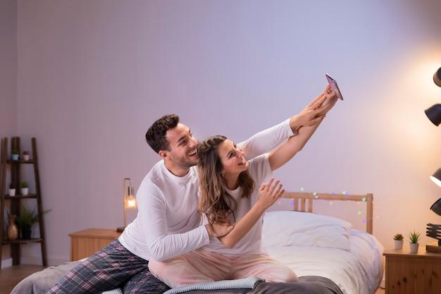 Couple heureux au lit prenant selfie