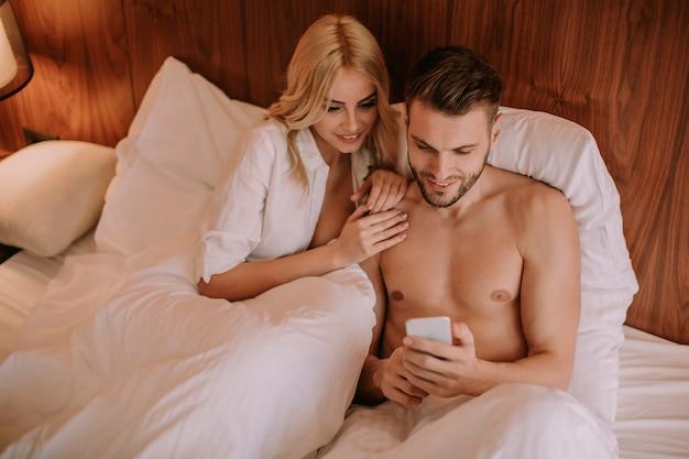 Couple heureux au lit et utiliser un téléphone mobile
