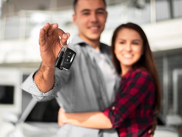 Couple heureux d'avoir acheté une nouvelle voiture