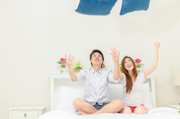 Couple heureux ayant une bataille d'oreillers à l'hôtel