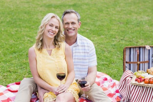 Couple heureux ayant un pique-nique avec du vin à l'extérieur