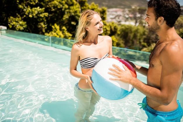 Couple heureux avec ballon de plage dans la piscine