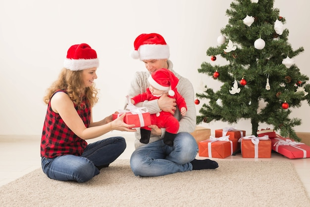 Couple Heureux Avec Bébé Célébrant Noël Ensemble à La Maison. Photo Premium
