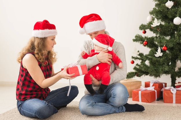 Couple heureux avec bébé célébrant noël ensemble à la maison.