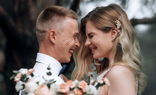 Couple heureux. belle jeune mariée et le marié avec un bouquet de mariée