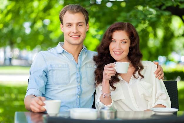 Couple heureux, boire un cappuccino en plein air