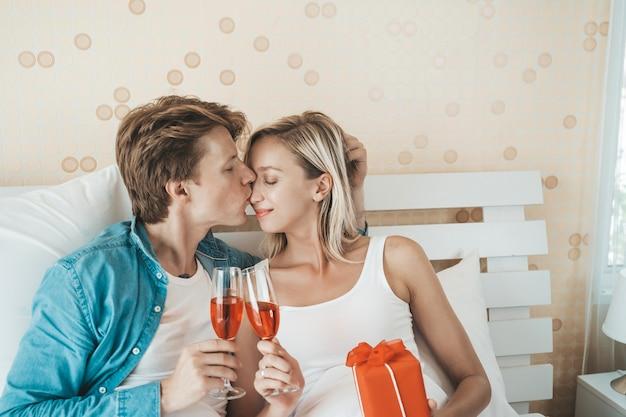 Couple heureux, boire du vin dans la chambre