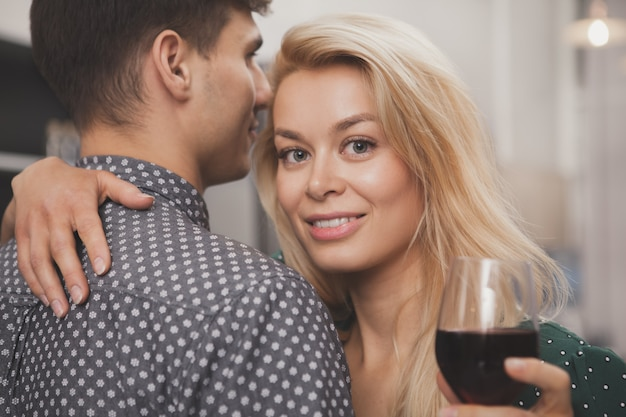 Couple heureux, boire du vin ensemble à la maison