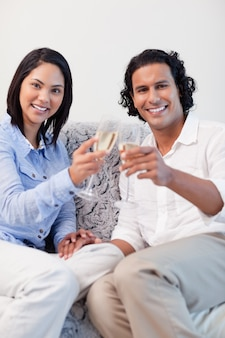 Couple heureux, boire du vin mousseux sur le canapé