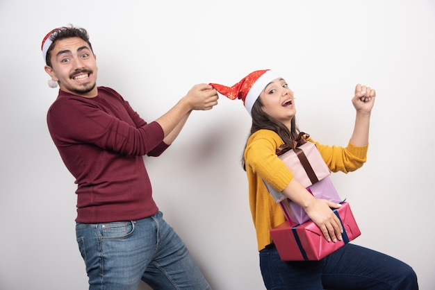 Couple heureux avec des cadeaux de noël sur un mur blanc.