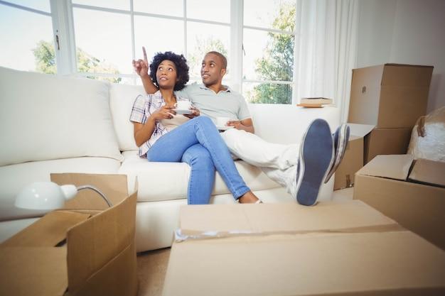 Couple heureux sur le canapé en train de prendre un café dans leur nouvelle maison