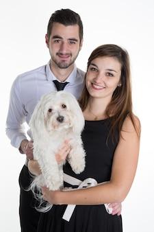 Couple heureux caresser leur chien blanc sur le canapé à la maison dans le salon