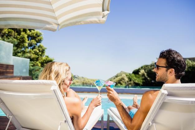 Couple heureux sur une chaise longue tenant des cocktails au bord de la piscine