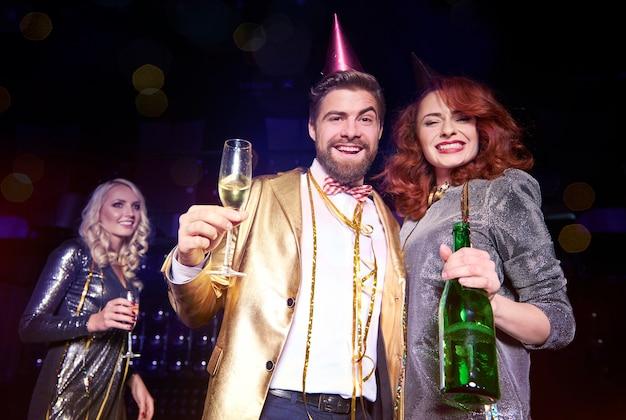 Couple heureux avec champagne célébrant le nouvel an