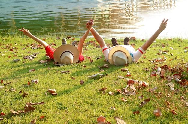 Couple heureux en chapeau de paille portant ensemble levant les bras avec le signe v au bord du lac
