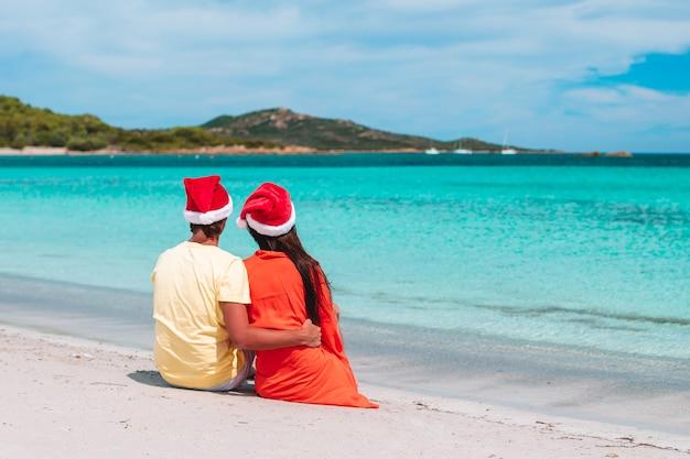 Couple heureux en chapeaux santa sur la plage