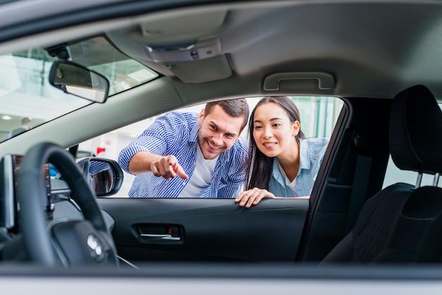 Couple heureux chez un concessionnaire automobile