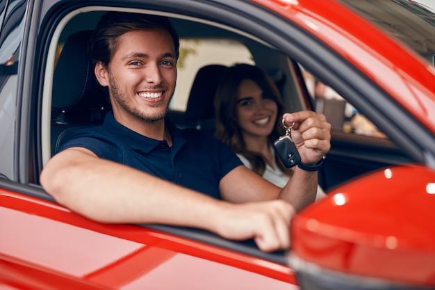 Couple heureux avec des clés en voiture