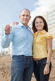 Couple heureux contre la nouvelle maison de brique