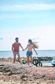 Couple heureux. un couple se tenant la main et courant sur une plage