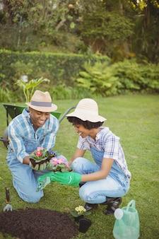 Couple heureux dans le jardin tenant des fleurs