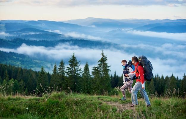 Couple heureux dans les montagnes pour marcher contre les belles montagnes,