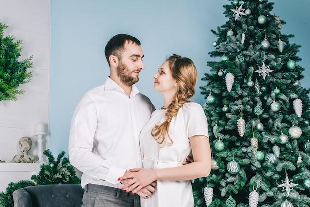 Couple heureux dans une salle blanche avec des décorations de noël