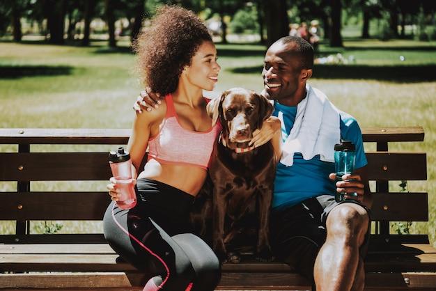 Couple heureux dans sportswear petting adorable brown dog