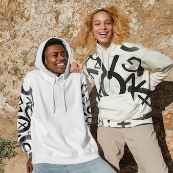 Couple heureux dans des sweats à capuche élégants pour un tournage en plein air en hiver