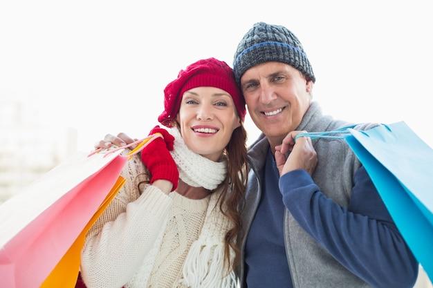 Couple heureux dans des vêtements chauds avec des sacs à provisions