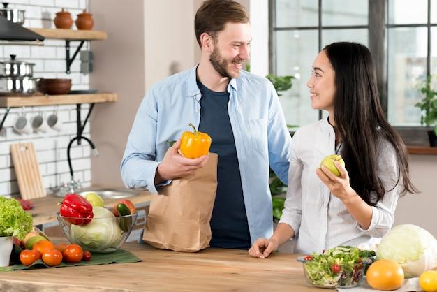 Couple heureux, debout, dans, cuisine, regarder, autre, dans, cuisine