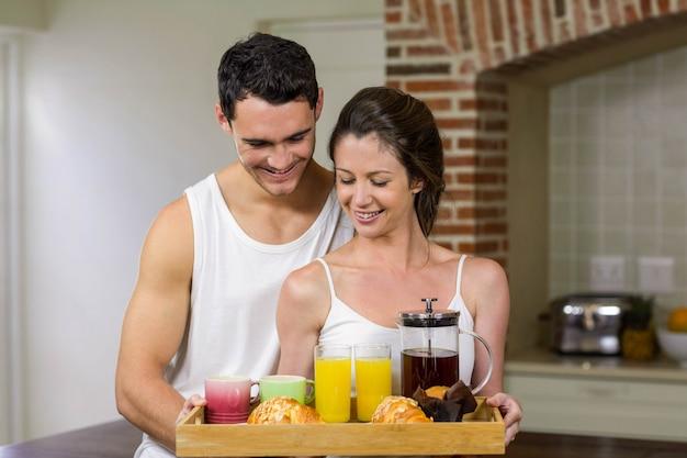 Couple heureux debout ensemble dans la cuisine avec plateau petit déjeuner sur plateau