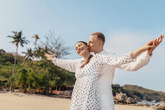 Couple heureux debout près des bras de la mer tendus à la plage. un homme mord doucement l'oreille de la fille