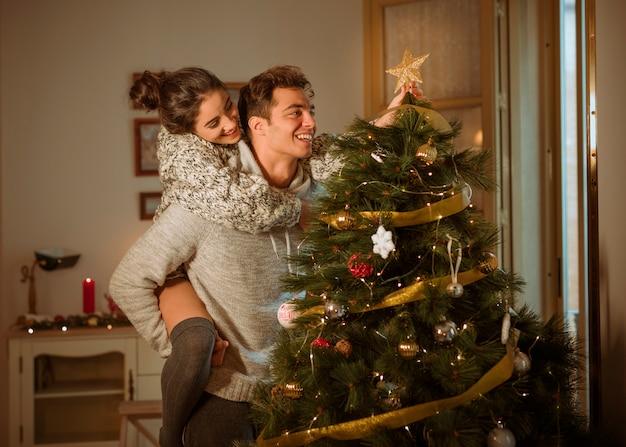 Couple heureux, décorer le sapin de noël avec étoile