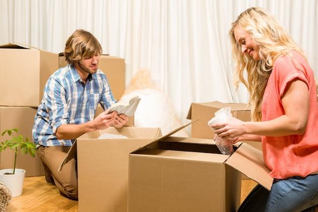 Couple heureux défaisant après le déménagement dans leur nouvelle maison