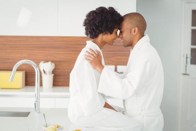 Couple heureux embrassant dans la cuisine à la maison