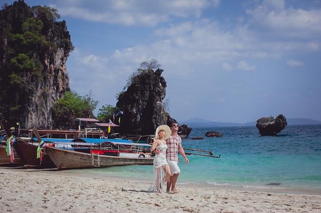 Couple heureux embrassant, marchant sur la plage contre la mer, les montagnes, les gondoles.