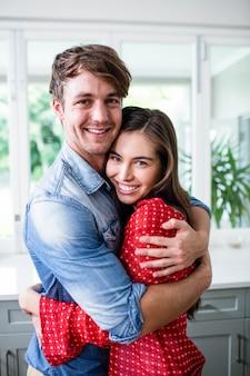 Couple heureux embrassant et regardant la caméra dans la cuisine