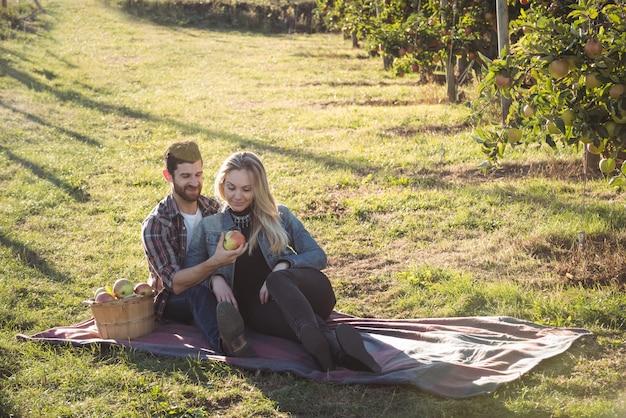 Couple heureux ensemble assis sur une couverture dans un verger de pommiers