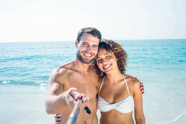 Couple heureux faisant selfie avec monopode