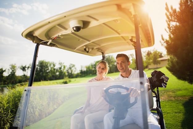 Couple heureux famille riche conduit la voiture de golf.