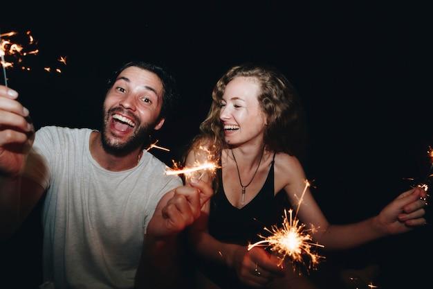 Couple heureux avec feux de bengale dans la nuit