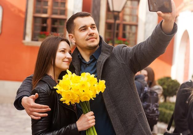 Couple heureux avec des fleurs faisant selfie dans la rue.