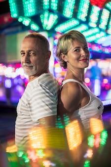 Couple heureux sur le fond des lampes incandescentes