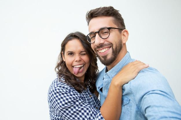 Couple heureux grimaçant et regardant la caméra
