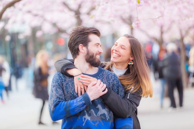 Couple heureux hipster à stockholm avec des fleurs de cerisier