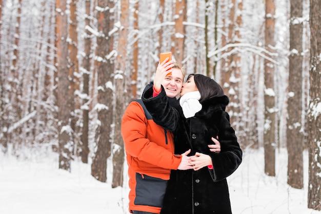 Couple heureux en hiver prenant des photos d'eux-mêmes avec un smartphone.