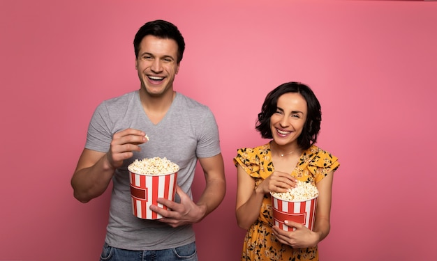 Couple heureux. homme et femme amoureux, qui rient, en mangeant du pop-corn et en regardant des films.