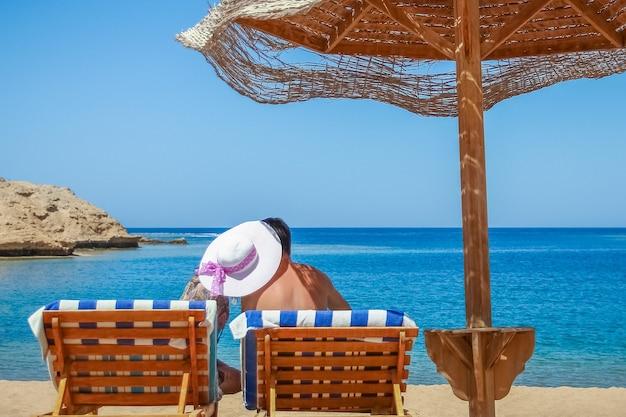 Un couple heureux homme et femme au bord de la mer voyageant sur la surface de vacances. un mec avec une fille sur une chaise longue sous la couverture ...
