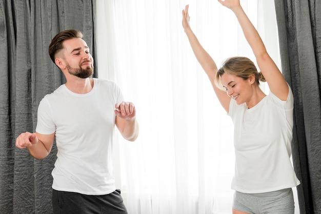 Couple heureux à l'intérieur portant des vêtements blancs